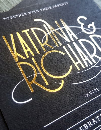 Gold foil stamp on textured black background, wedding invitations designed and printed by Pinc
