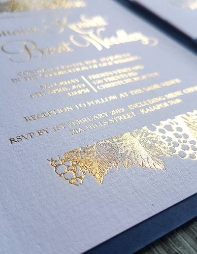 Intricate gold foil detailing on vineyard themed wedding invitation designed by Pinc