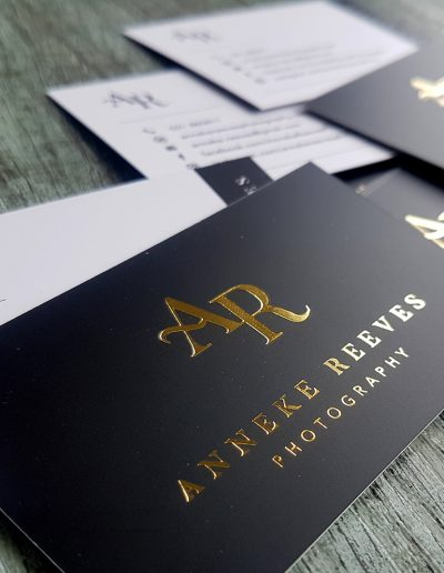 Gold foil logo on white business cards with printed black and matte laminate coating