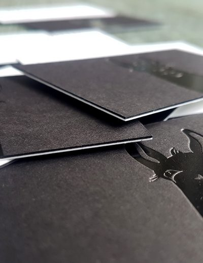 Black and white sandwiched business cards with gloss black foil logo