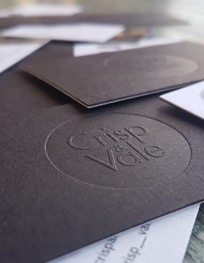 Debossed circle resulting in a raised logo design, black card bonded with white card
