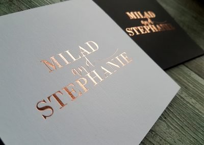 Close up of blush foil on textured white card with matching black sleeve