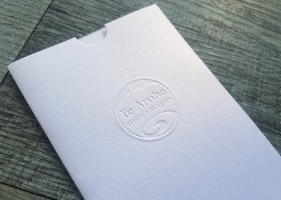 Metallic white DLE voucher sleeves with custom embossed logo for Te Aroha Mineral Spas