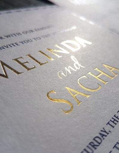 Close up of gold foil stamped names on a thick white card stock
