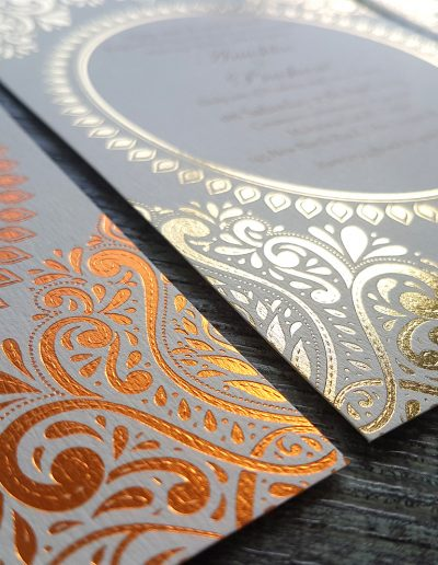 Close up of an intricate copper and gold pattern on wedding invitations