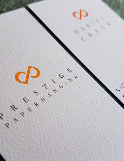 Copper foil logo pressed into both sides of a textured white business card