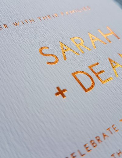Close up of copper foil stamped into textured white card