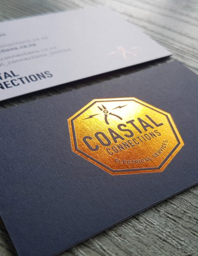 Copper foil logo pressed on to navy card sandwiched with white card