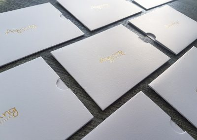 Metallic white gift voucher sleeves customised with gold foil stamped logo