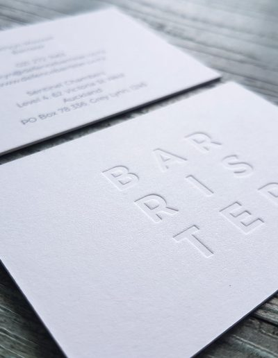 Blind debossed logo pressed into textured white card