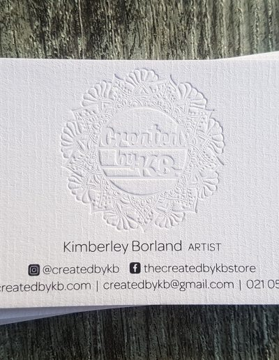 Intricate logo design indented into textured white card