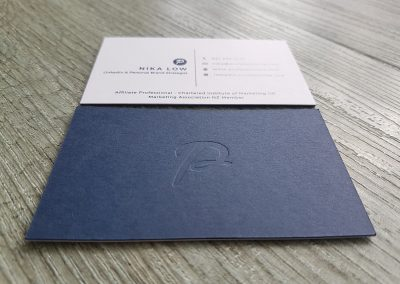 Debossed logo on navy card sandwiched with white card, design and print by Pinc