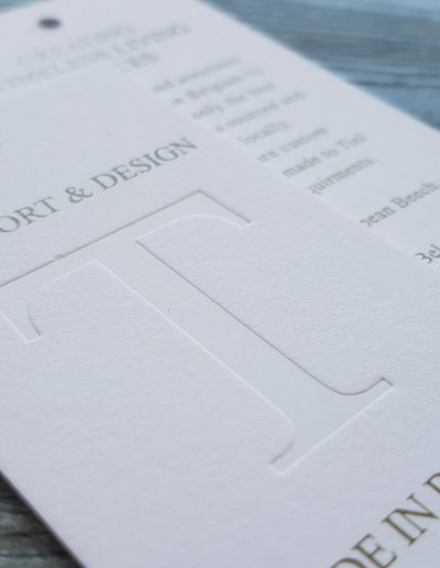 Thick swing tags on a pulpy white card stock with debossed logo