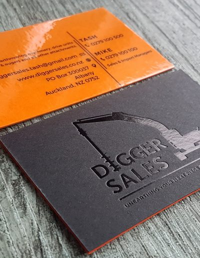 Gloss black foil on matt black card, sandwiched with orange card and gloss laminate