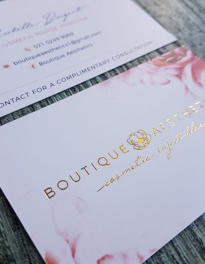 Gold logo stamped logo on pink floral business cards on a smooth white card stock