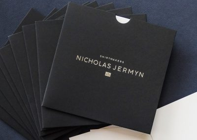 Custom printed gift voucher sleeves - silver foil logo on navy blue sleeves
