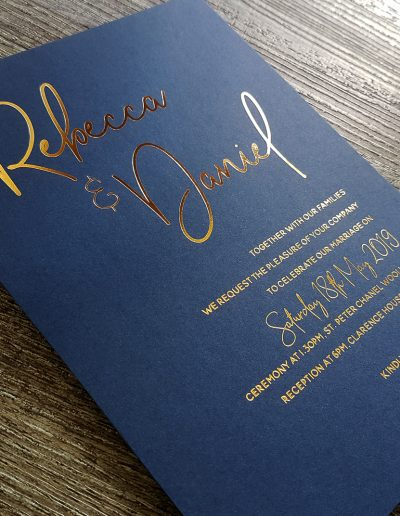 Gold foil text pressed into a navy blue card stock