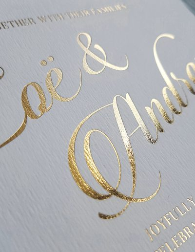 Close up of gold foil stamped into thick textured white card