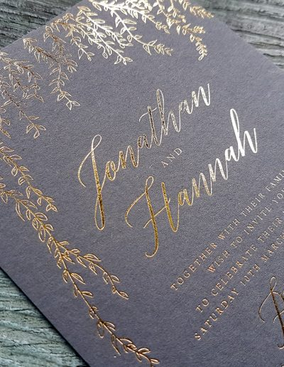 Gold foil pressed wedding invitation in to charcoal card