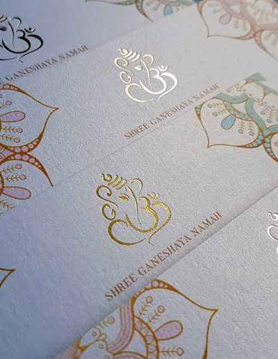 Gold foil stamped Ganesha symbol on metallic white Indian wedding invitations designed and printed by Pinc