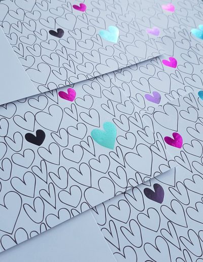 Kindercare cards printed with their branding colours of pink, purple and teal foil