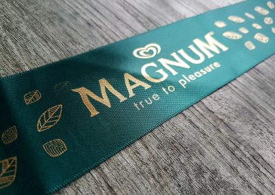 Gold logo for Magnum on teal coloured ribbon
