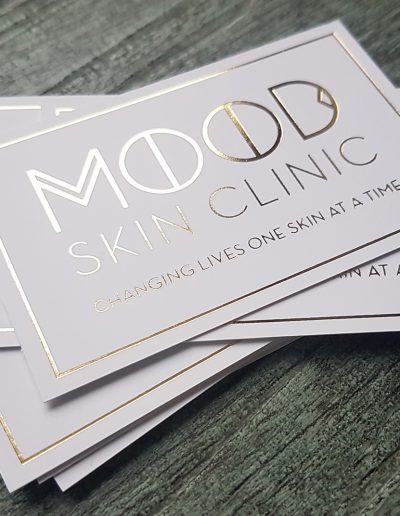 Mood Skin Clinic gold appointment cards on a smooth white silk stock