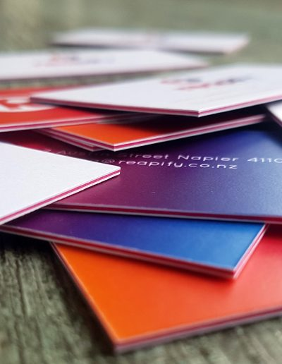Colourful business cards as a 3 layer sandwich with bright pink card in between