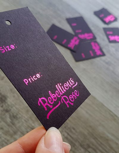 Swing tags on black card, printed in a pink foil