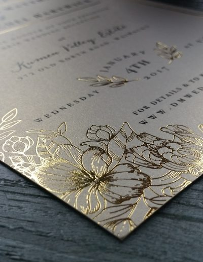 Close up corner of a gold floral invitation
