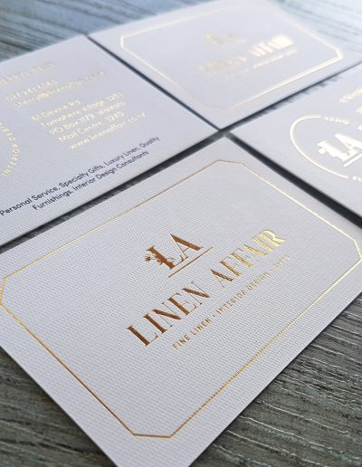 Gold foil stamps on textured white business cards