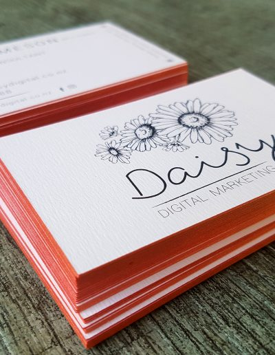 Rose gold sides on textured white business cards for Daisy Digital Marketing