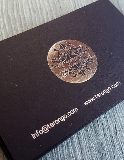 Silver foil stamped business cards printed on a thick black card stock
