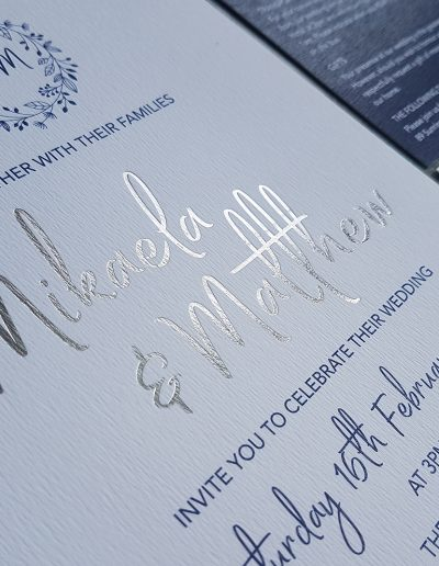 Close up of silver foil stamped names onto white textured card