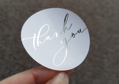 Thank you printed in silver foil on white circle stickers