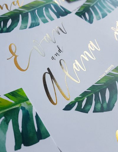 Wedding invitations with gold foil names and tropical, botanical imagery