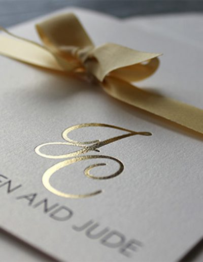 Gold foil initials on metallic ivory card